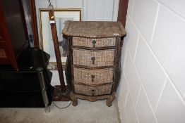 A wicker bombe shaped chest of four graduated drawers