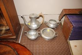 A pewter spot hammered three piece teaset; and a small twin handled bowl, similar
