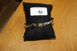 A white metal and tigers eye bangle