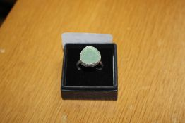 A green stone and white metal mounted dress ring
