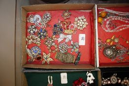 A tray of various decorative costume brooches