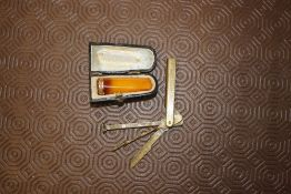 A cased amber and yellow metal cigar holder; and a