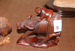 A carved hardwood figure of a boy riding a water b