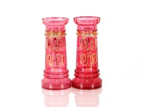 A pair of cranberry vases, with blue enamel floral decoration heightened in gilt, 23cm high