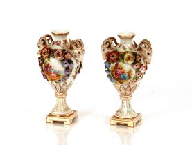 A pair of Dresdenurns,profuse floral encrusted decoration and rams head masks, 19cm high