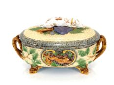 A Minton Majolica game pie dish and cover,decorated gun dog and shooting apparel to the lid, the