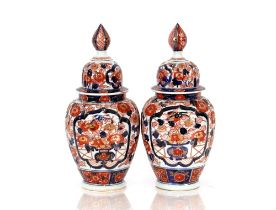 A pair of 19th Century Japanese Imari porcelain vases and covers, the ribbed bodies painted with