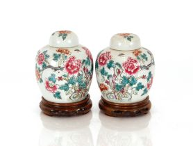 A pair of Chinese Famille Rose ginger jars,and covers raised on carved hardwood stands, 20cm high
