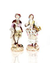 A pair of 19th Century German porcelain figures,depicting street vendors in brightly coloured