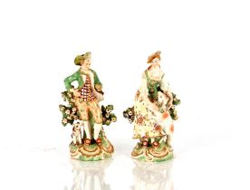 A pair of 19th Century porcelain figures,depicting shepherd and shepherdess, with floral