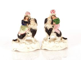 A pair of Victorian Staffordshire spill holders,in the form of a maid and youth with oversized
