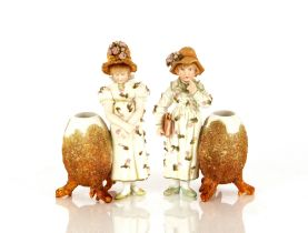 A pair of Victorian bisque ware posy holders,in the form of two girls with floral encrusted
