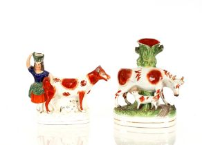 A Victorian Staffordshirespill holder,in the form of cow and suckling calf, 29cm high, 22cm
