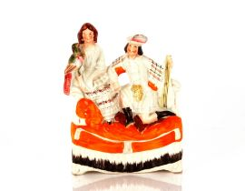 A Victorian Staffordshire flat back figure group,depicting seated couple with a parrot, 26cm high