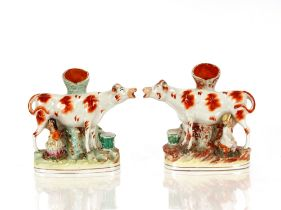 A pair of Victorian Staffordshire flat back spill holders, in the form of cows being milked, 22cm