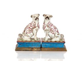 A pair of continental porcelain pug dogs,raised on brass plinth bases, 19cm high
