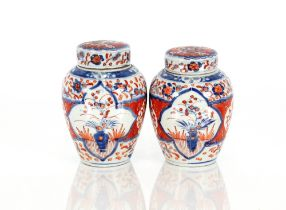 A pair of Japanese Imari patterned ginger jars and covers, with inner lids surmounted by bamboo