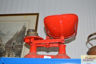A set of red painted kitchen scales and weights