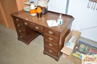 A mahogany desk fitted nine drawers