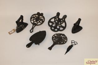 Four various ornate cast iron trivets; two flat ir