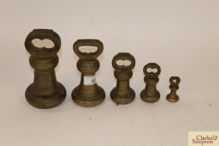 A graduated set of four brass bell weights and a