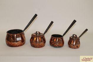 Four antique copper graduated saucepans (two with