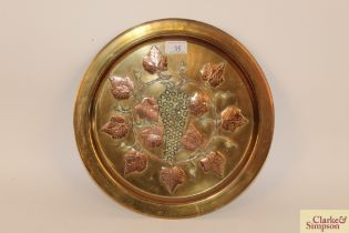 A brass and copper plaque with vine decoration