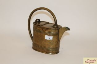 An antique brass watering can with loop handle