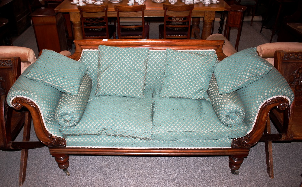 A Victorian mahogany scroll end sofa,having carved decoration and raised on turned baluster