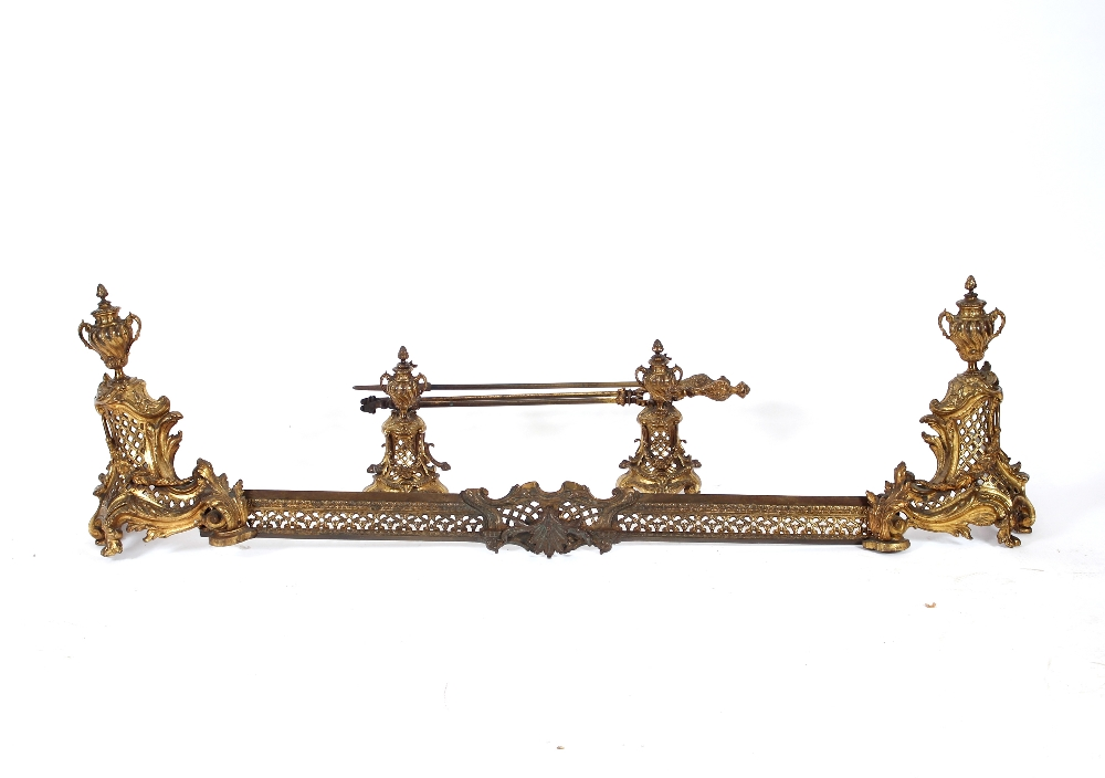 A French Rococodesign gilt metal fireplace set,comprising extending fender, implement rests, and