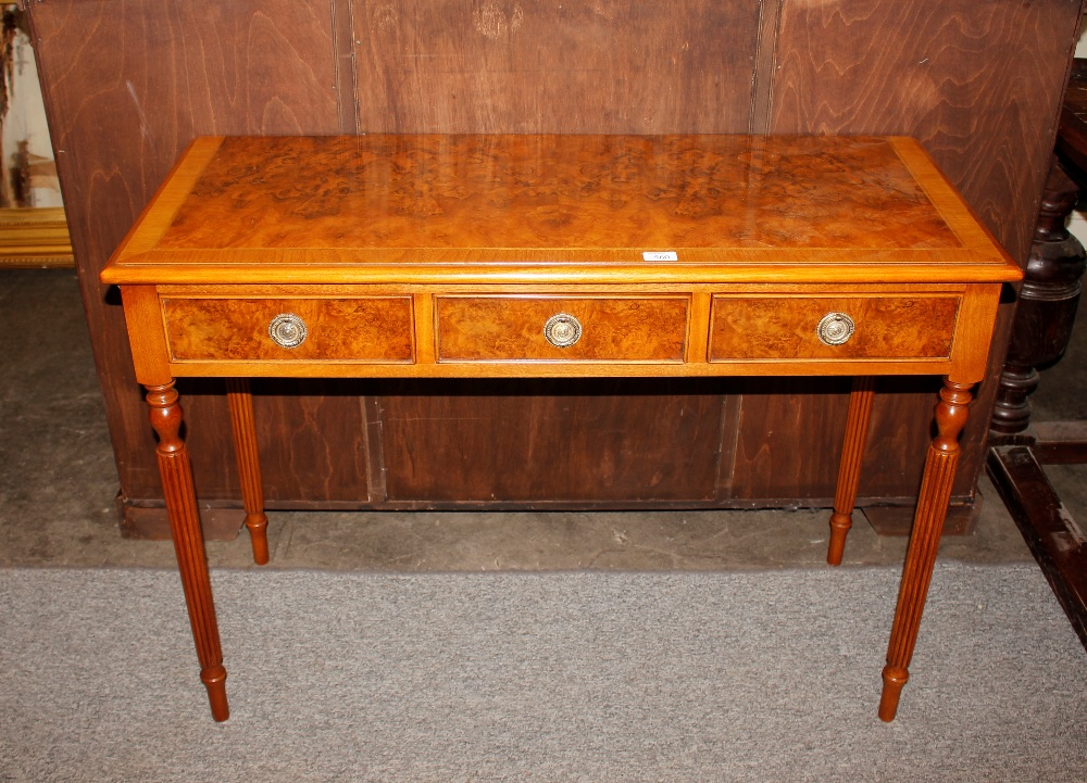 A walnut cross banded and herringbone strung three drawer hall table,raised on reeded tapering