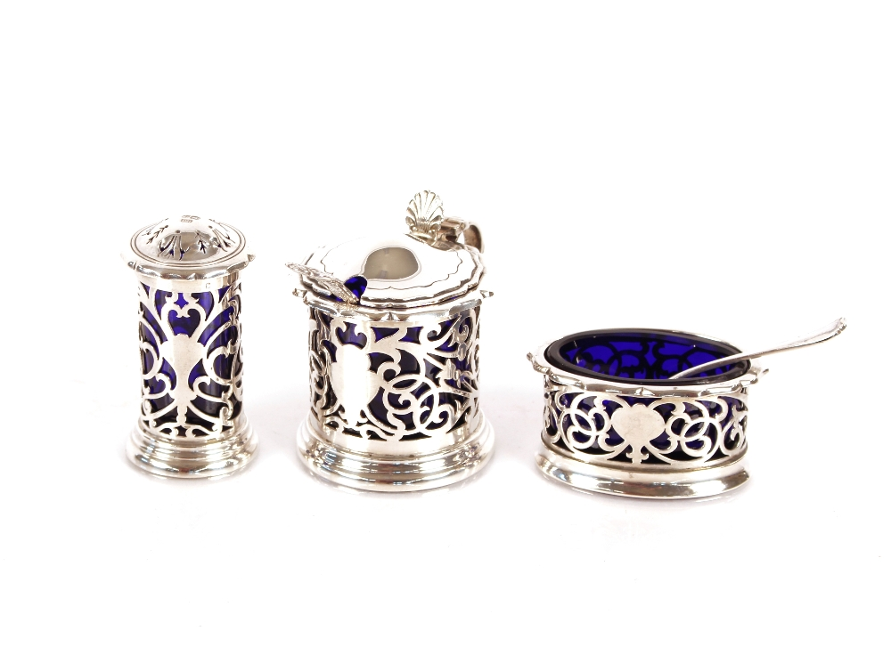 A three piece silver condiment set,having shaped borders and pierced sides, blue glass liners, by