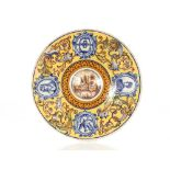 An 18th Century continental pottery charger,the raised central boss decorated with a river scene,