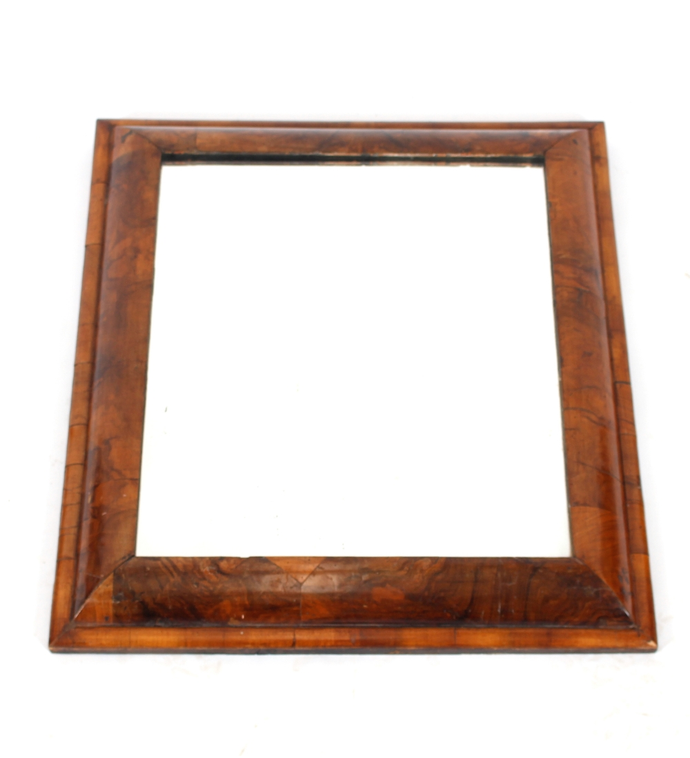 An antiquewalnut cushion framed wall mirror,55cm x 51cm