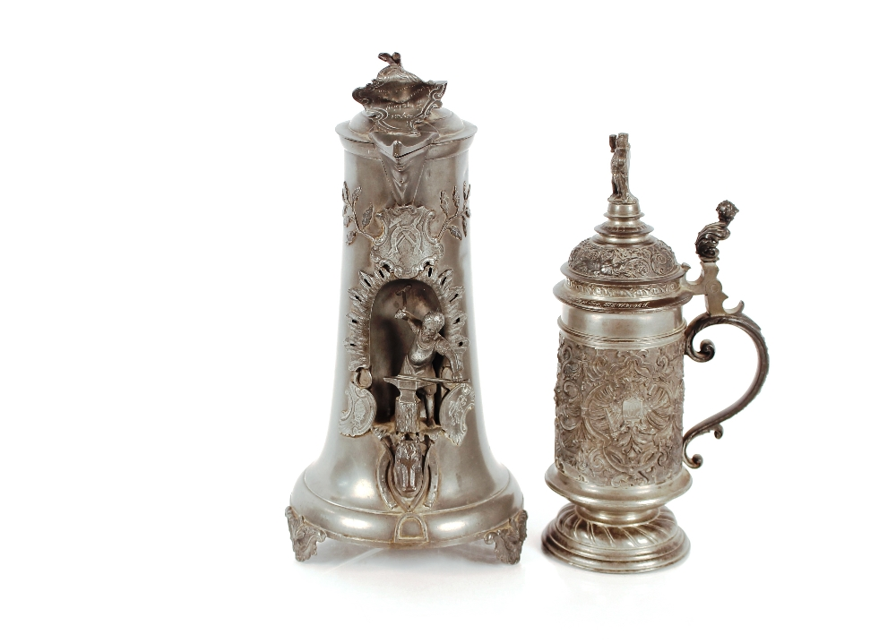 A 19th Century continental pewter flagon,decorated with figure of a blacksmith at work, having