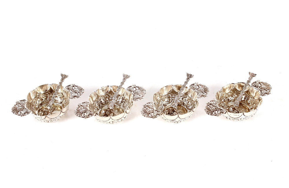 Four late Victorian silver salts,with matching spoons having embossed foliate decoration and