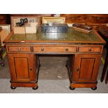 A Victorian golden oak and ebonised pedestal writing desk,the leather inset top above three