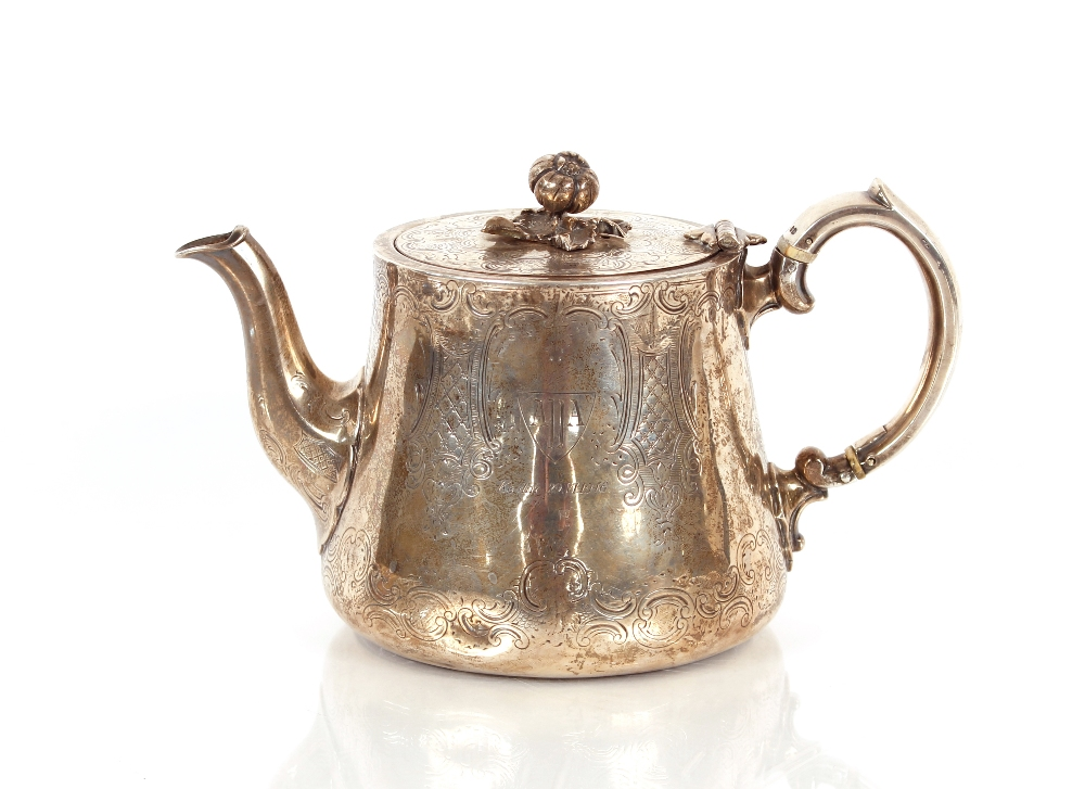 A Victorian silver teapot,having all over foliate scroll decoration around a central cartouche with