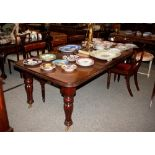 A mahogany extending dining table,in the Victorian manner fitted extra leaf and raised on