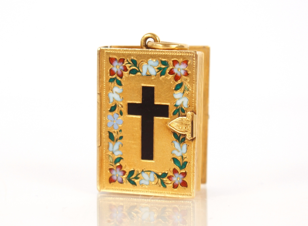 A yellow metal and enamel decorated mourning pendant,in the form of a Bible, containing hair