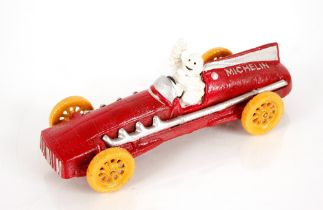 A cast iron Michelin style racing car and figure,