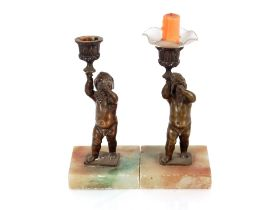 A pair of bronzed cherub candlesticks, raised on s