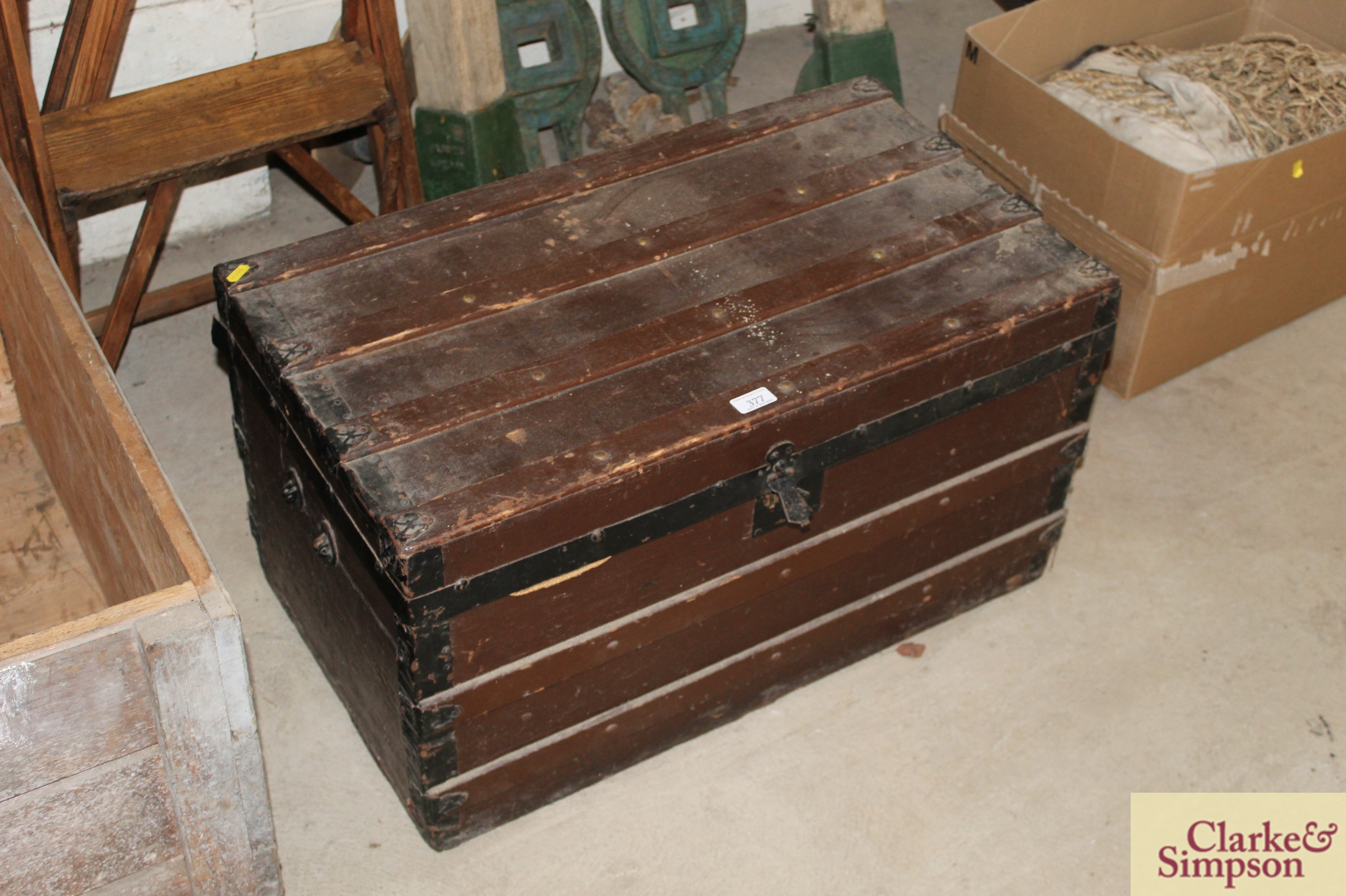 A vintage wooden trunk with metal mounts and carry