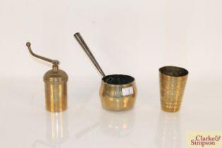 An antique brass saucepan with cast iron handle, a
