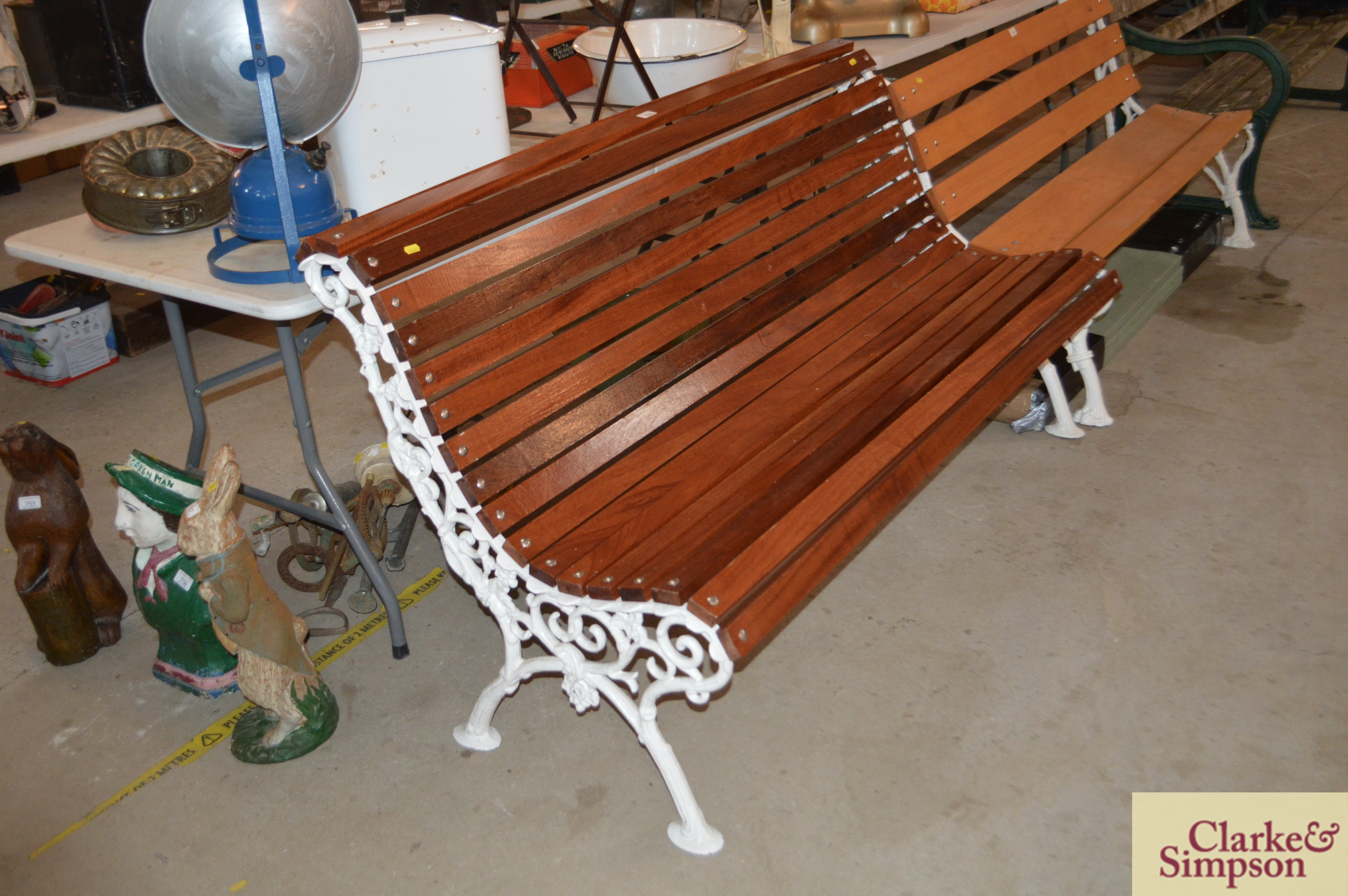 An ornate cast iron and teak slatted roll top benc
