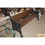 A cast iron and wooden slatted park bench, dated 1