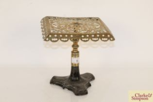 An antique brass hearth stand on cast iron base