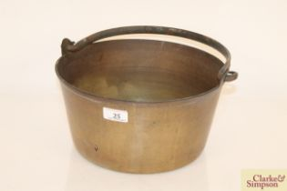 A heavy brass preserve pan with swing handle