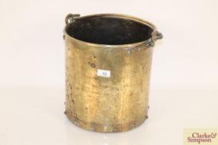An antique brass coal bucket