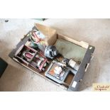 A box containing a vintage foot pump, a battery ch